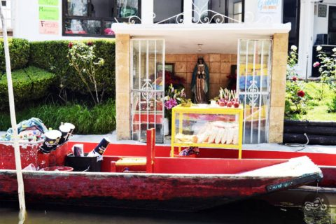 A vendor's boat pulled along the shore. For sale are micheladas, popcorn, and candied apples.