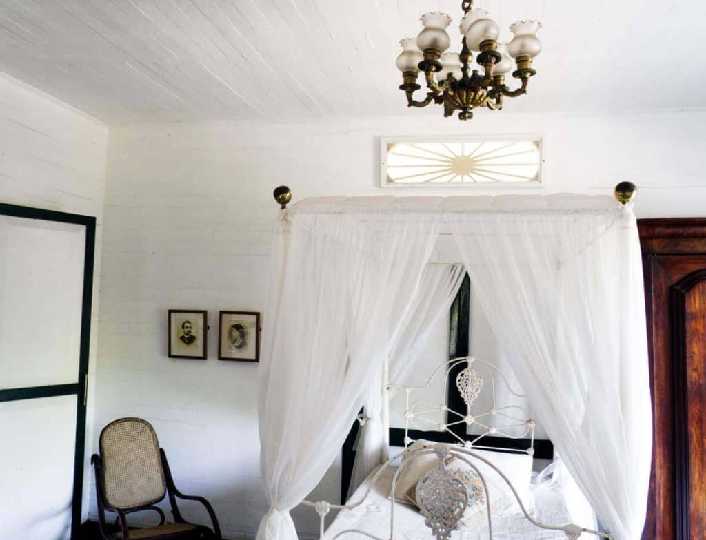 A canopy bed draped in white located in a bedroom at the House of Rafael Nunez.