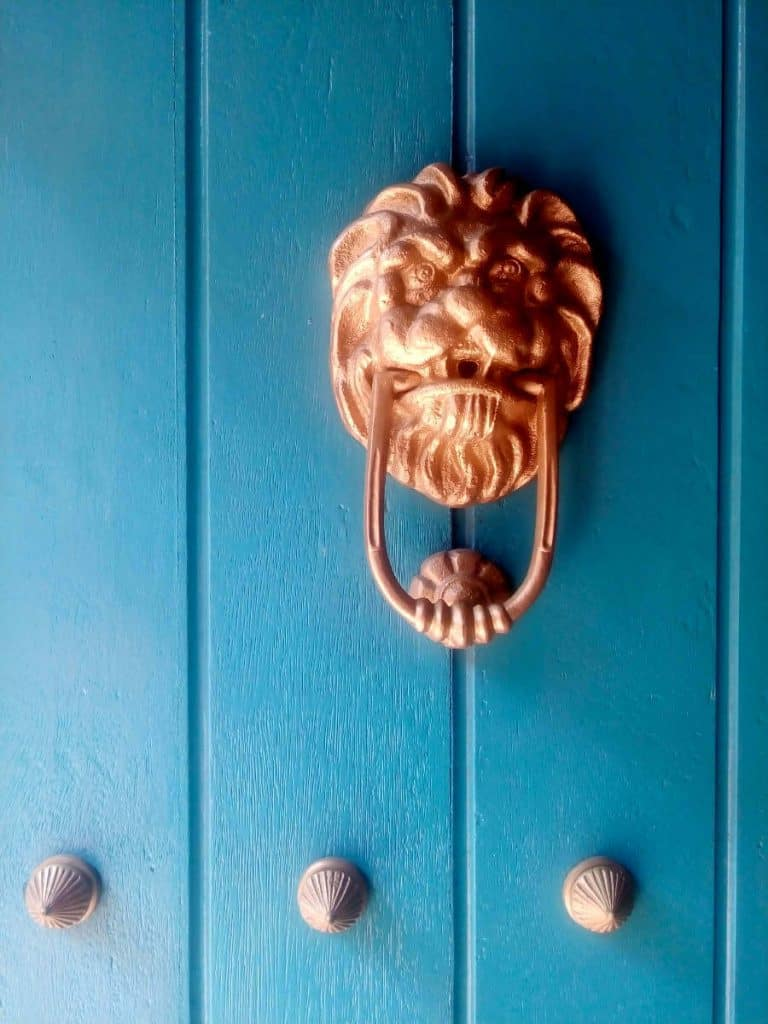 A metal lion's face door knocker on a turquoise door in Cartagena, Colombia.