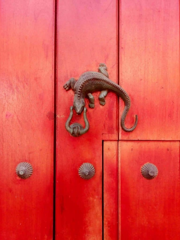 A metal lizard door knocker hung on a red door in Cartagena.