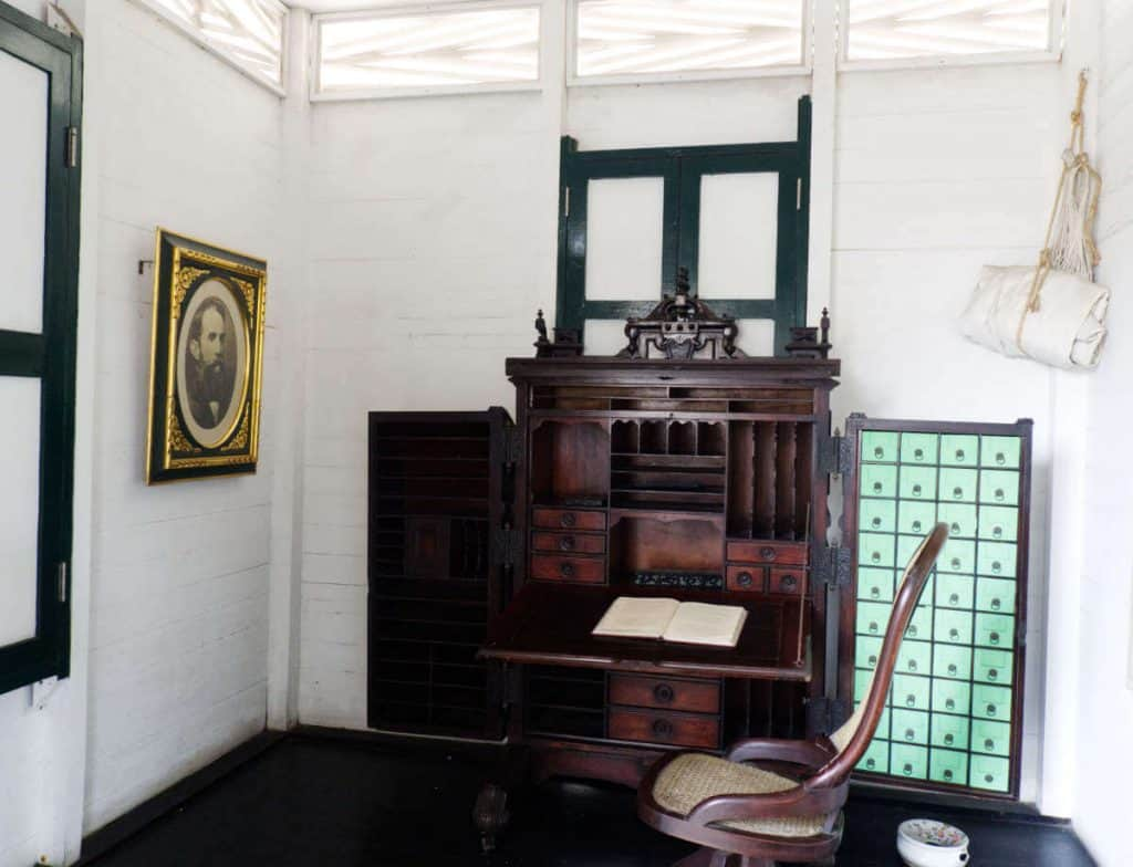 An interior view of the office at the Rafael Nunez House, complete with a desk, portrait, and rolled hammock hanging in the corner.